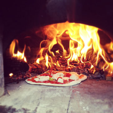 Cooking a pizza in a wood fueled oven